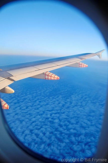photo of wing taken out airplane window above the clouds