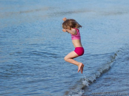 young girl jumping waves at the water's edge