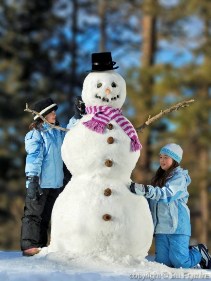 Two girls building snowman - model released