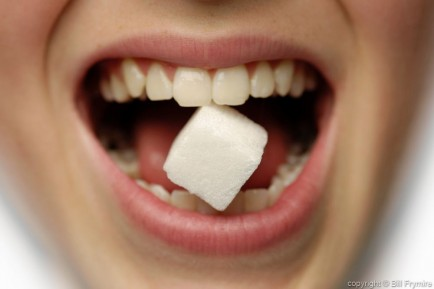 Girl with sugar cube in her teeth