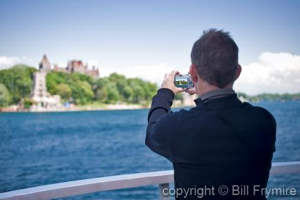 Man taking photo of Boldt Castle in the Thousand Islands, USA - model released