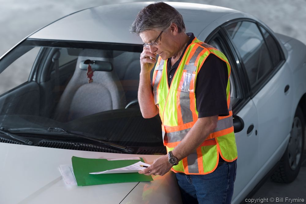 An image of a man looking at papers in a safety vest.